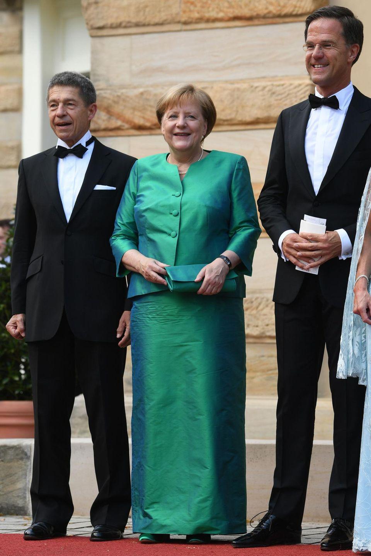 Mit einem Lächeln posiert unsere Kanzlerinzusammen mit ihrem Mann Joachim Sauer und dem niederländischem Premierminister Mark Rutte auf der Eröffnungsfeier desBayreuth Festivals. Auffällig ist, dass Merkels allzeit geliebter Blazer auch in ihrer Abendgaderobe einen besonderen Stellenwert einnimmt. In beschichteter Optik kombiniert sie einen flaschengrünen Blazer zum farblich abgestimmten, knielangen Rock.