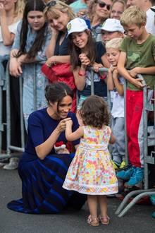 Tag 15  Herzogin Meghan hat besonders die niedlichen Zwerge Neuseelands ins Herz geschlossen. Bei ihrem Besuch in der StadtRotorua geht Harrys Ehefrau wieder tief in die Hocke, um sich von dem niedlichen Mädchen auf Augenhöhe begrüßen zu lassen.