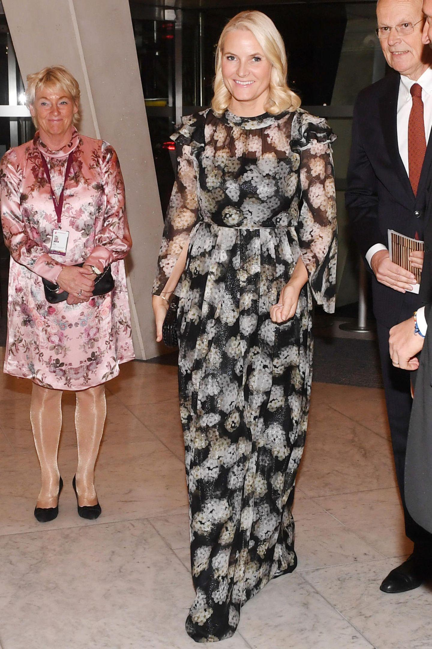 Mette-Marit trägt ein bodenlanges Abendkleid in schwarz-weiß des Labels Ole Yde. Das Kleid besticht mit seinem feinen, eleganten Stoff, einem hübschen Blumenmuster und verspielten Details.