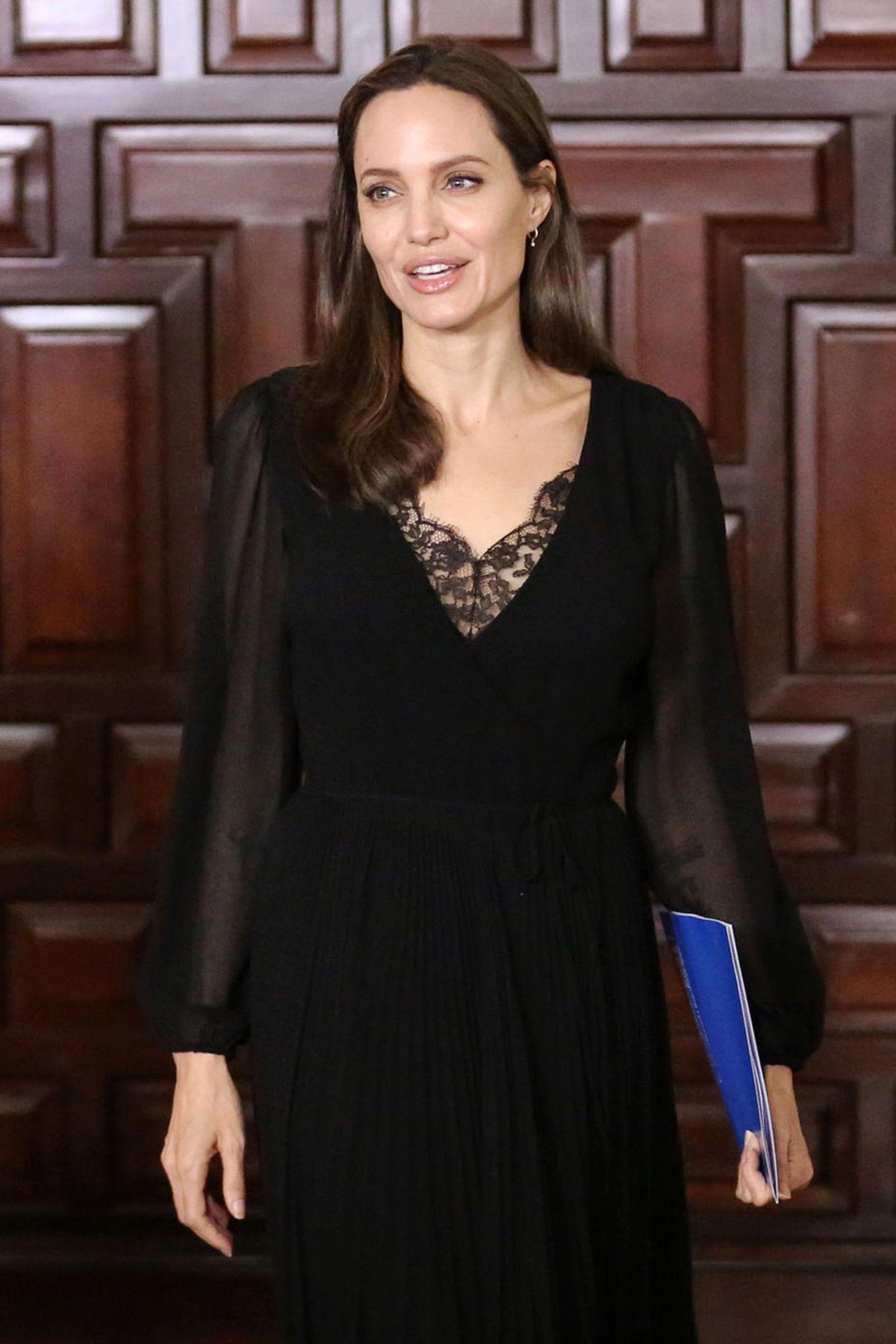 So raffiniert kann ein schwarzes Kleid sein: Angelina Jolies Modell verführt mit einem Spitzen-Einsatz im Dekollekté-Bereich, transparenten Ärmeln und einem Rock in feinen Plissees.