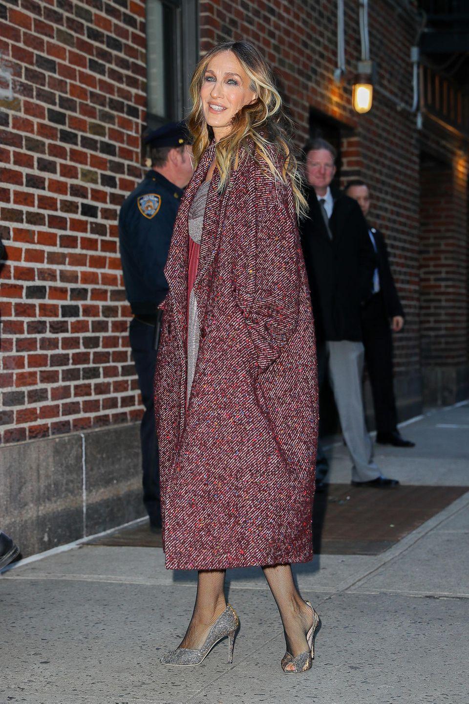 Auf dem Weg zur Late Show mit Stephen Colbertin New York City zeigtsich Schauspielerin Sarah Jessica Parker mit einem überdimensional großen Tweed-Mantel in der Farbe Brombeere. Was SJP wohl unter diesem Mantel trägt?