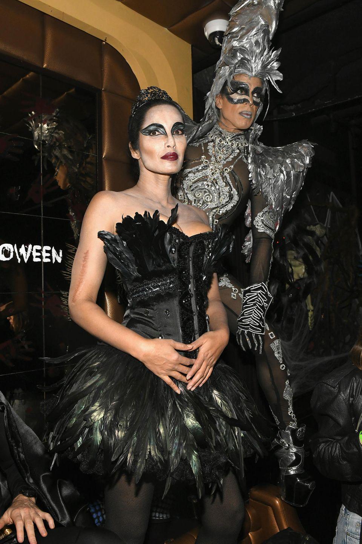 """Padma Lakshmi erobert die Tanzfläche als """"Black Swan""""-Ballerina, neben ihr schreitet Jorge Gonzalezauf Mega-Plateau-Heels als Glitzervogel herein."""