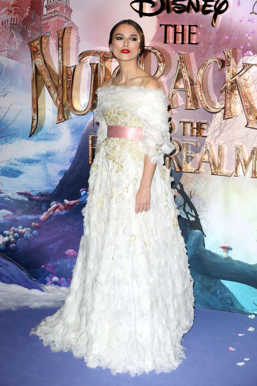 """Chanel-Fan und """"Zuckerfee"""" Keira Knightley hat sich für ihrenAuftritt auf dem blauen Teppich der """"Nussknacker""""-Premiere diesesprinzessinhafte Kleid im weißen Blüten-Look ausgesucht."""
