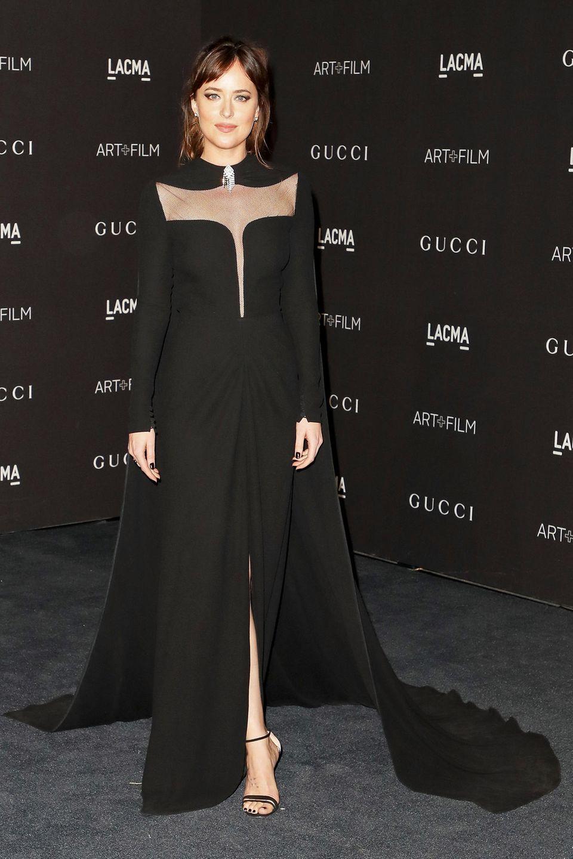 Elegant und geheimnisvoll wirkt Dakota Johnson im schwarzen Cape-Kleid von Gucci.