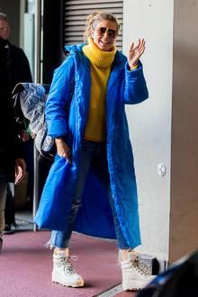 Heidi Klum zeigt sich bei ihrer Ankunft in Berlin nicht nur in bester Laune, sie verbreitet im langen, blauen Mantel von A Plan Application kombiniert mit gelben Woll-Rolli auch welche.