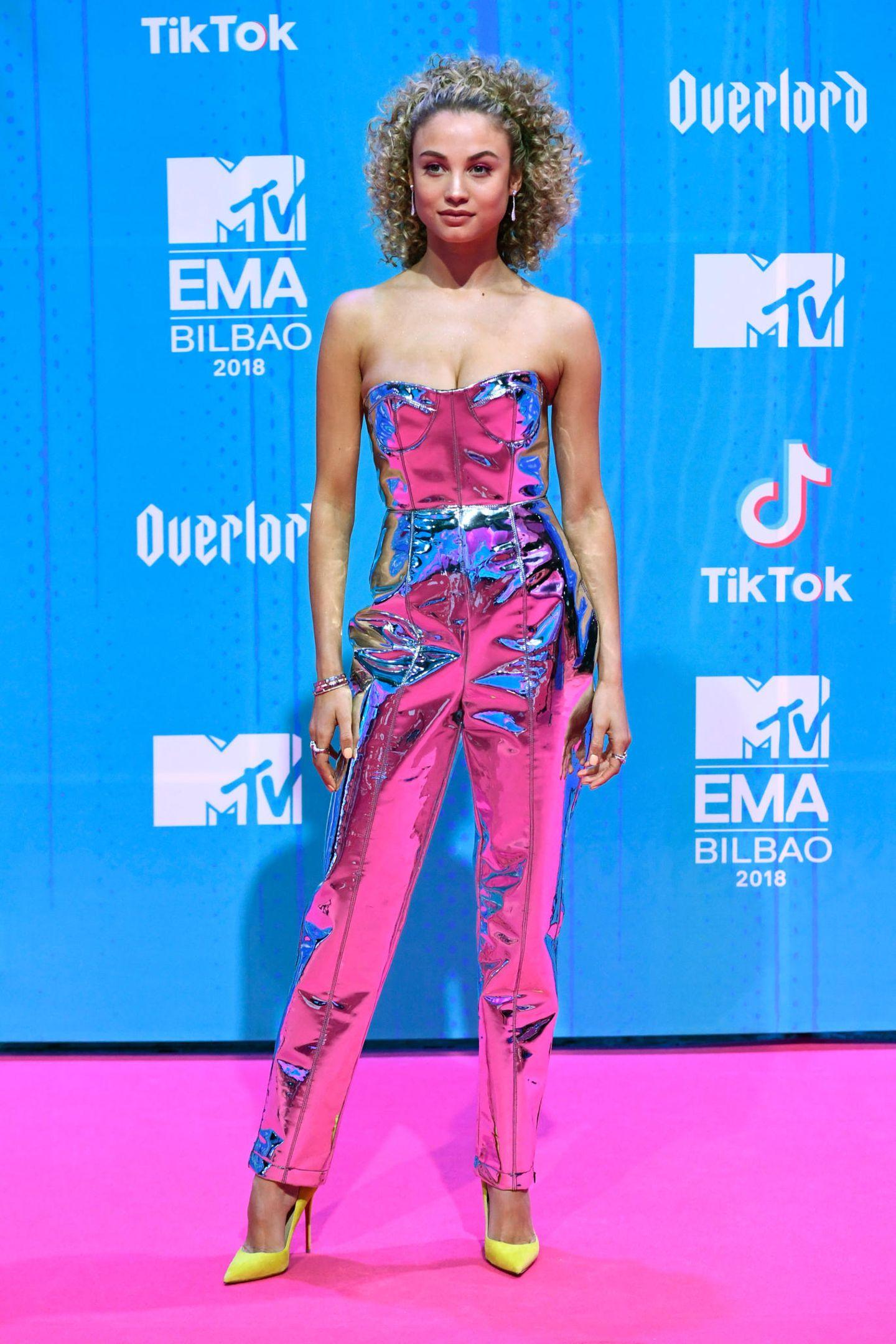 Rose Bertram schlüpft in einen Metallic-Jumpsuit, der die Farbe des pinken Teppichs wiederspiegelt.