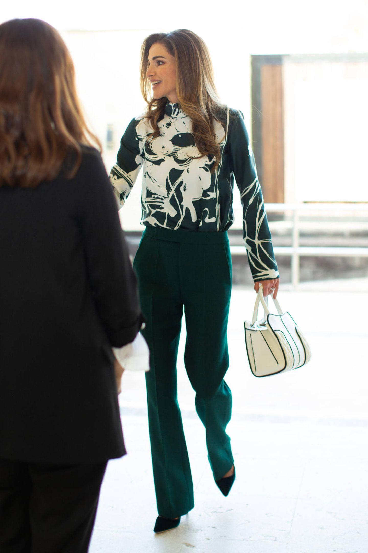 """In einem grün-weißen Komplettlook besucht Königin Rania ein Meeting der """"Jordan River Foundation"""". In der Hand hält sie eine farblich abgestimmte Tasche von Tod's, dazu trägt sie dunkelgrüne Pumps von Manolo Blahnik."""