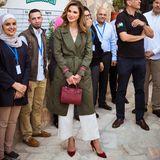 Auch bei diesem Look ist alles perfekt abgestimmt: Der herbstliche Rotton ihrer Schuhe findet sich auch in der edlen Tasche und den Ärmelschlaufen des Mantels wieder. Der khakifarbene Trenchcoat und die weiße Culotte runden den elegant-legeren Stil von Königin Rania ab.