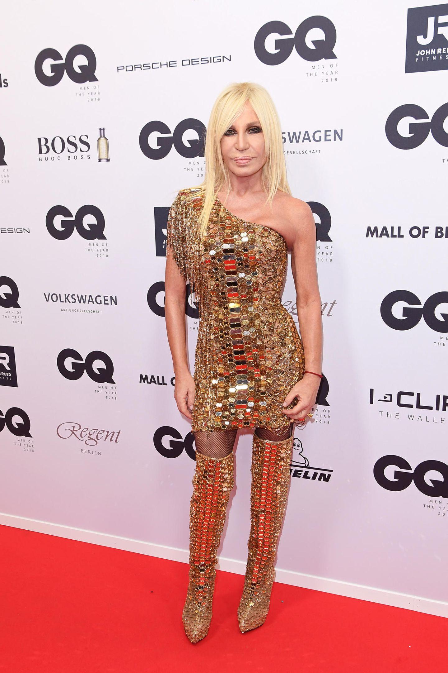 """Donatella Versace weiß, wie ein Auftritt auf dem roten Teppich auszusehen hat. Sie funkelt im goldenen Minikleid und freut sich über die Auszeichnung der """"Fashion Icon""""."""