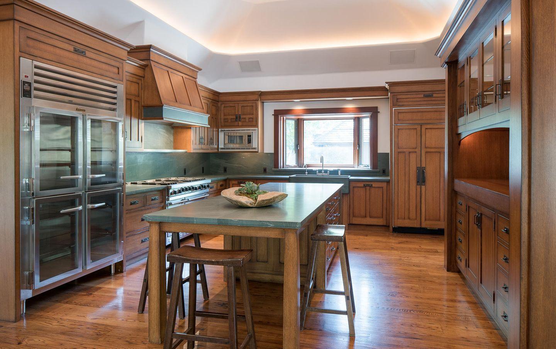 Die geräumige Küche strotzt vor natürlichen Materialien: Alle Möbel sind aus Holz, während die Tisch- und Arbeitsplatten aus Naturstein gefertigt sind.