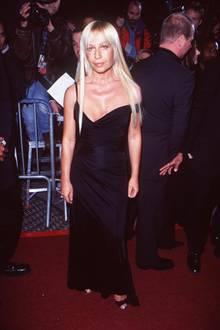 """Die damals 42-jährige Donatella Versace erscheint auf den """"Vogue Fashion Awards""""in einem bodenlangen schwarzen Kleid mit tiefem Dekolleté. Bis heute behält sie ihrplatinblond-gefärbtes Haar bei."""