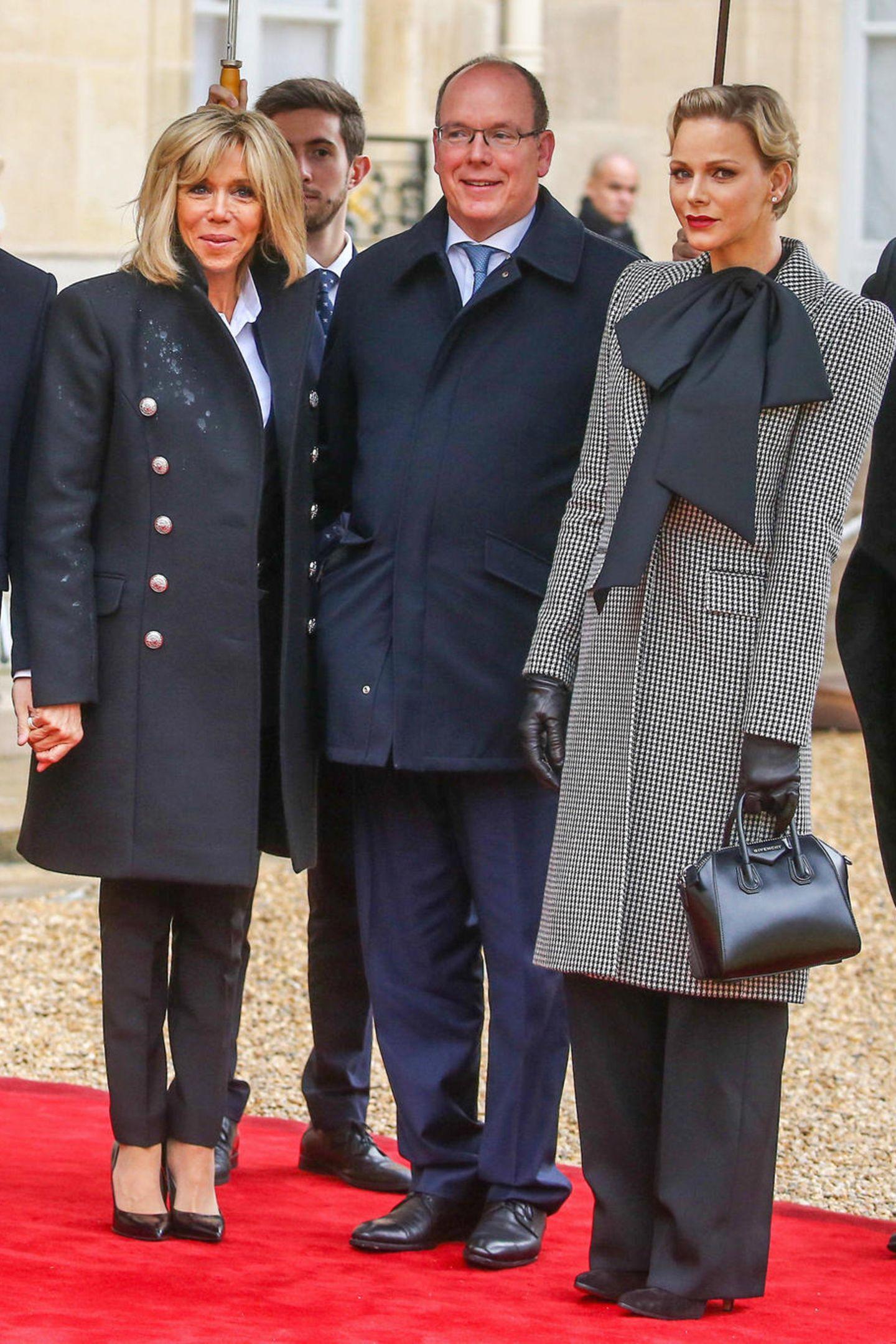 Fürstin Charléne kombiniert zu einer schwarzen, weiten Hose eine schwarze Bluse mit einer überdimensionalen Schleife. Über diesem Look trägt sie einen schwarz-weißen Mantel im Hahnentrittmuster.