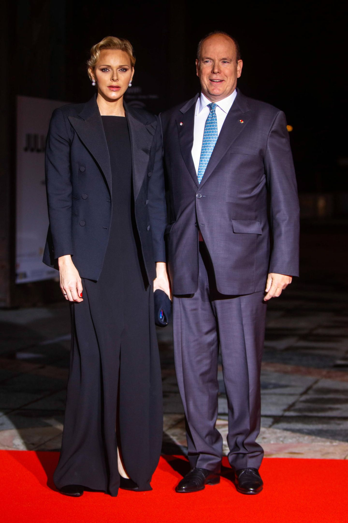 Zum Staatsdinner in Paris zeigt sich Fürstin Charlène in einer bodenlangen Abendrobe mit sexy Beinschlitz. Dazu kombiniert sie einen Blazer.