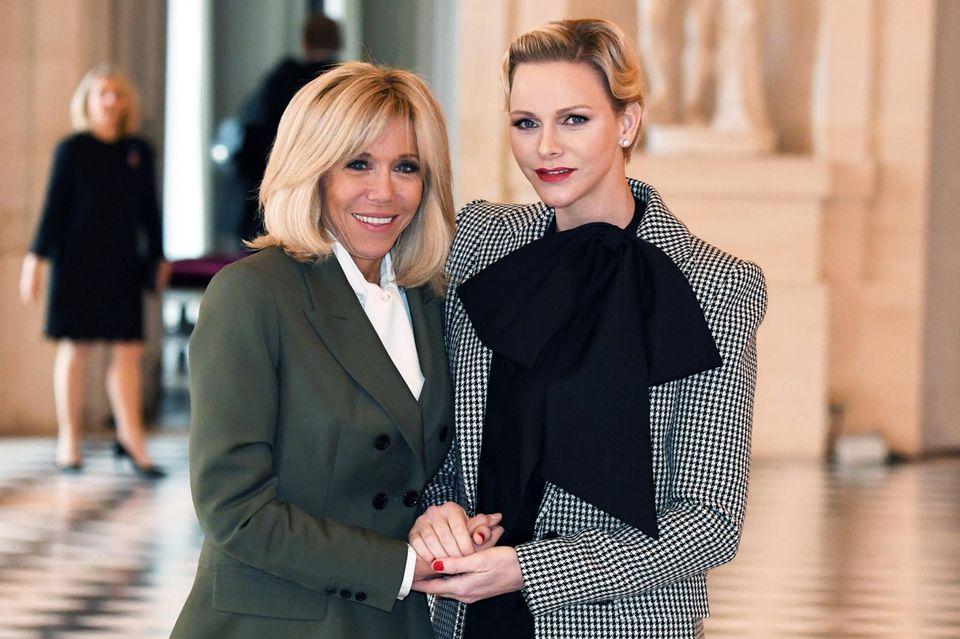 Was für ein hübsches Duo! Fürstin Charlène von Monaco wird von Frankreichs First Lady Brigitte Macronvor den Feierlichkeiten zum 100-jährigen Jubiläum der Beendigung des ersten Weltkrieges am Élysée-Palast empfangen. Auffällig ist dabei vor allem Charlènes Make-up-Look und eine riesige, schwarze Schleife um ihren Hals ...
