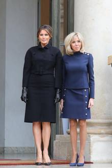 In einem schwarzen Kleid von Bottega Venetaund mit passenden Lederhandschuhen zeigt sich Melania Trump neben Brigitte Macron vor dem Elysee Palast in Paris. Der Taillengürtel betont ihre schmale Silhouette zusätzlich. Ein wahrer Hingucker sind jedoch ihre Schuhe...