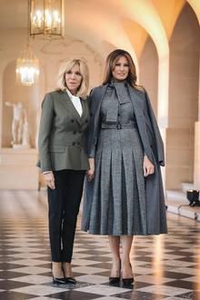 Melania Trump schafft es, auch in Grau zu strahlen. In einem Midikleid von Dior mit ausgestelltem Faltenrock und Schleifendetails zeigt sie sich neben Brigitte Macron, Frankreichs First Lady. Ihren grauen Mantel hat sie sich lässig über die Schultern geworfen.