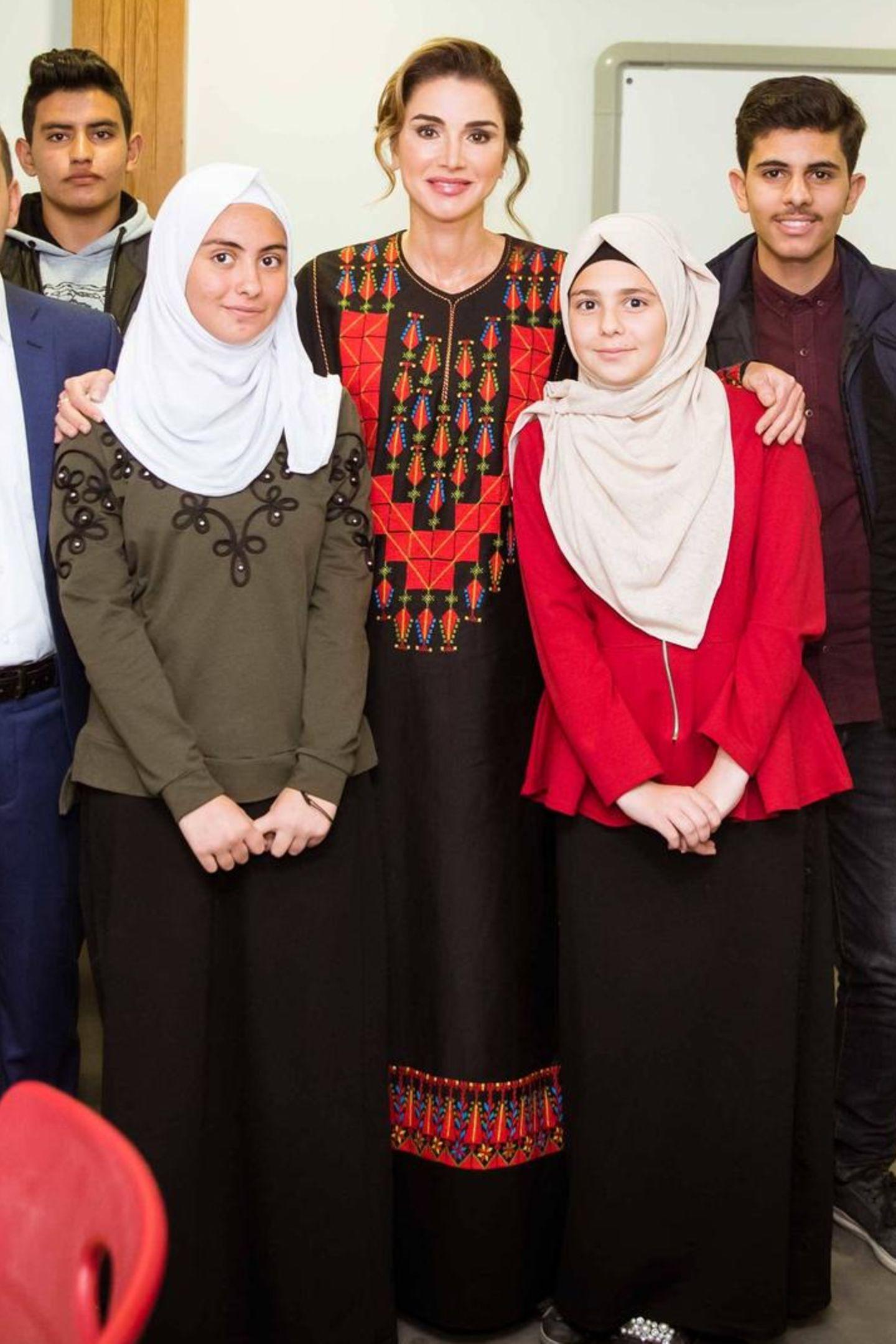 Während ihres Besuchs im Kulturzentrumtrifft Rania zahlreiche Mitglieder der ansässigen Gemeinde. Beim Posieren mit der Gruppe fällt auf: Die farbigen Stickereien am Kleid der Königin finden sich auch am Saum wieder.
