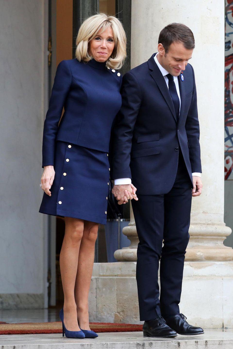 First Lady Brigitte Macron hat definitiv eine Vorliebe für Blautöne und Knopf-Details. Für ein Meeting mit Melania Trump wählt Brigitte eine raffinierte Kombination aus Oberteil und Rock.