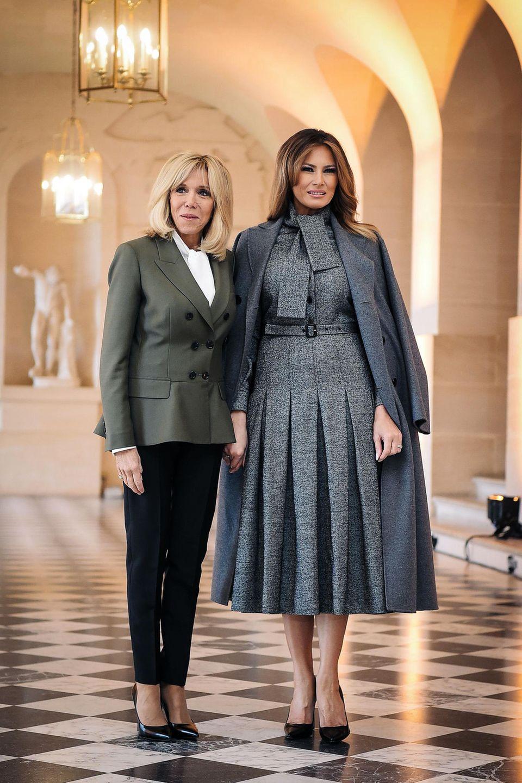 Der Style von Frankreichs First Lady Brigitte Macron ist unverwechselbar. Die Blondine wählt stets klassische Looks und sticht mit ihrer Stilsicherheit so manch andere Dame aus. Während der Feierlichkeiten zum 100-jährigen Jubiläum der Beendigung des ersten Weltkrieges, trifft sie auch auf Melania Trump. Während Brigitte auf eine schwarze Hose, eine weiße Bluse und einen khakifarbenen Blazer setzt, zeigt sich Melania ganz ladylike in einem grauen Midi-Kleid.