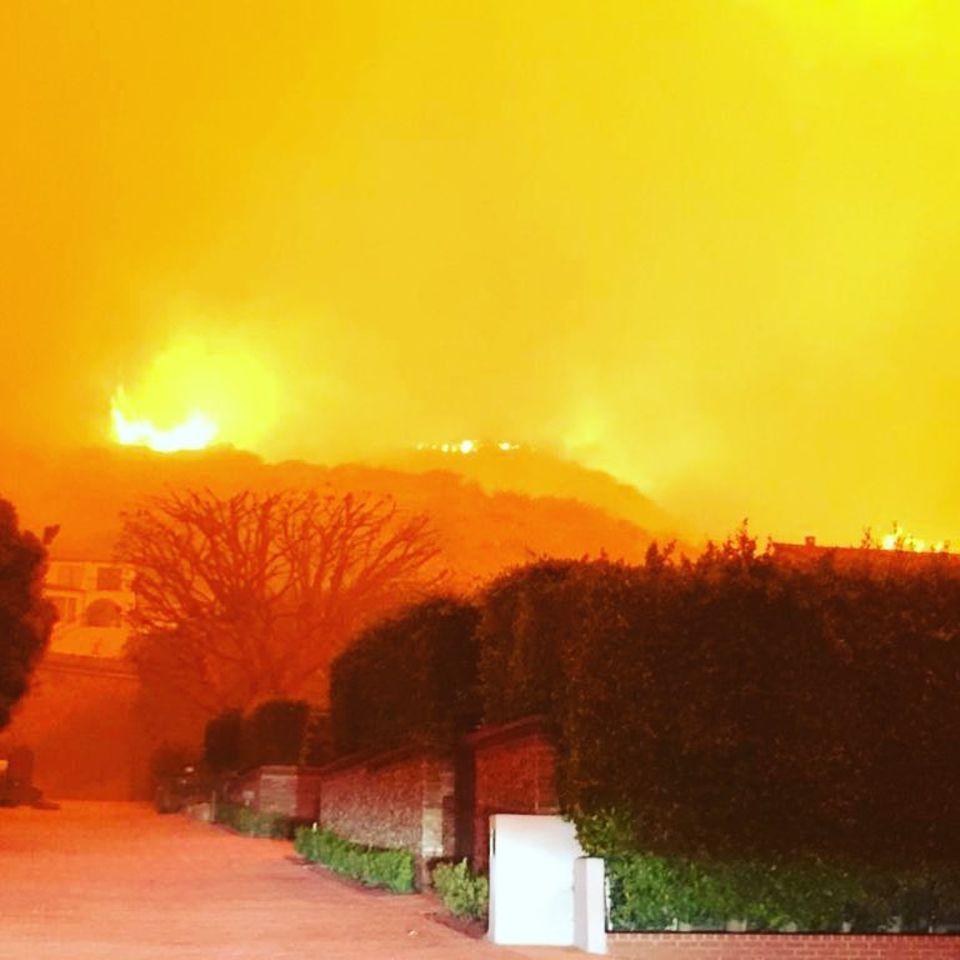 Die Flammen fressen sich bedrohlich nah an das Haus heran.