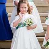 Als Blumenkind bei Prinzessin Eugenies Hochzeit bezaubert Prinzessin Charlotte in einem weißen Kleidchen, von dem sich ein grünes Seidentuch mit feinem Blumenmuster perfekt abhebt. Eine helle Strumpfhose sowie weiße Schuhe machen den Look wundervoll engelhaft.