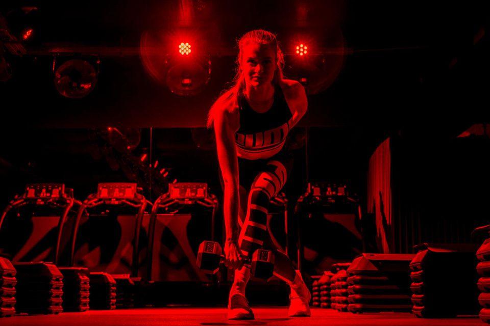 Im Urban Heroes in Hamburg ist der Raum in rotes Licht getaucht, die Musik spielt laut aus den Boxen. Die Atmosphäre reißt Tabea mit. An den Steps bringt sie mit Gewichten ihre Muskeln zum Glühen.