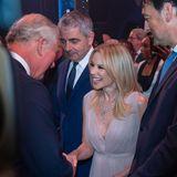 """Während der Vorstellung von """"We Are Most Amused and Amazed"""" trifft Prinz Charles (links) auf Sängerin Kylie Minogue und Comedian Rowan Atkinson (Mitte), besser bekannt als: Mr. Bean."""