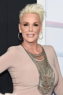 Beim Gang über den roten Teppich New York setzt Brigitte Nielsen auf auffällige, glitzernde Accessoires. Zu dem schlichten Abendkleid kombiniert sie eine große Statementkette sowie silberne Kreolen. Ihre kurzen blonden Haare stylt die Schauspielerin wild nach oben.