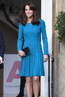 Anderthalb Jahre später tritt die Herzogin erneut in dem Kleid mit gelegten Falten auf. Schon wieder hat sie die schwarze Clutch dabei, die einen viel zu starken Kontrast zu dem Türkis bildet.  Wie gut, dass sie diese in 2018 weglässt.