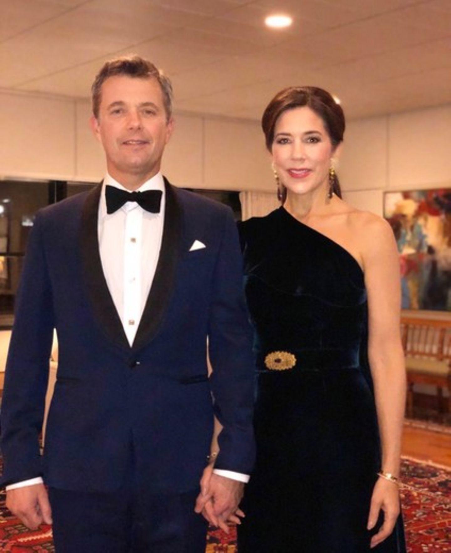 Prinz Frederik und Prinzessin Mary lassenes sich nicht nehmen, den 70. Geburtstag von Prinz Charles in London zu feiern. Für das Dinner wähltMary ein langes One-Shoulder-Abendkleid aus dunkelblauem Samt. Ihre Taille wird durch einen gleichfarbigen Gürtel mit einer goldenen Brosche betont, den Brustbereich verzieren Volants. In Sachen Schmuck setzt die dänische Kronprinzessin auf lange Ohrringe und passende Armbänder, die Haare trägt sie hochgesteckt. Prinz Frederik wählt einen klassischen Smoking, passt sich aber der Farbwahl seiner Ehefrau an. Das royale Paar gibt sich zu diesem Anlass überraschend privat - Händchen haltend strahlen sie in die Kamera.