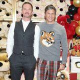 """Während Neil Patrick Harris auf einen schlichten Nadelstreifenanzug setzt, hat sein Mann David Burtka für das """"FAO Schwarz Grand Opening-Event"""" einen weihnachtlichen Fuchs-Pullover gewählt."""