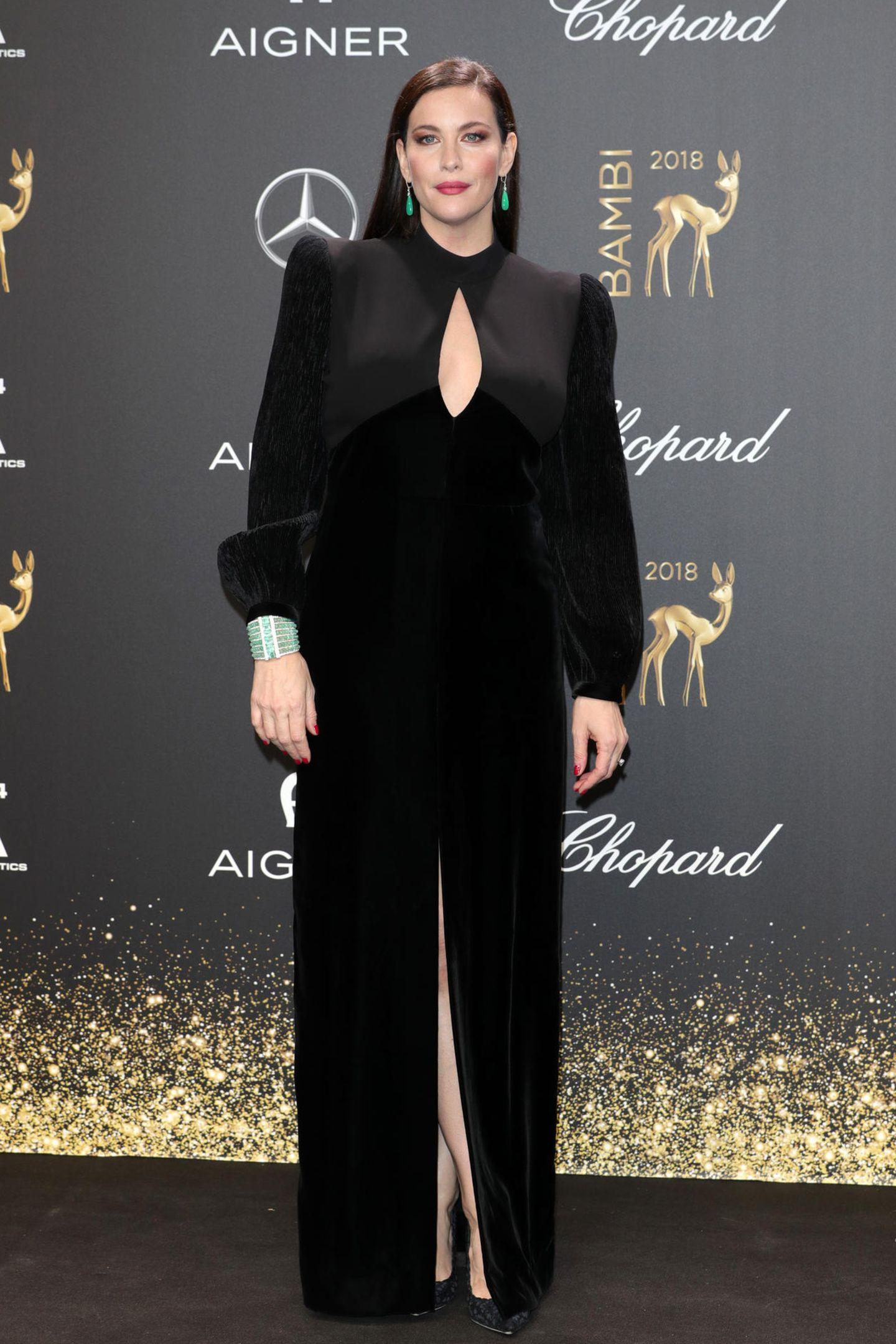 """Liv Tyler zeigt, dass""""hochgeschlossen"""" nicht immer """"verschlossen"""" sein muss. Ihr schwarzes Kleid hat einen Tropfen-Ausschnitt samt leichtem Kragen."""