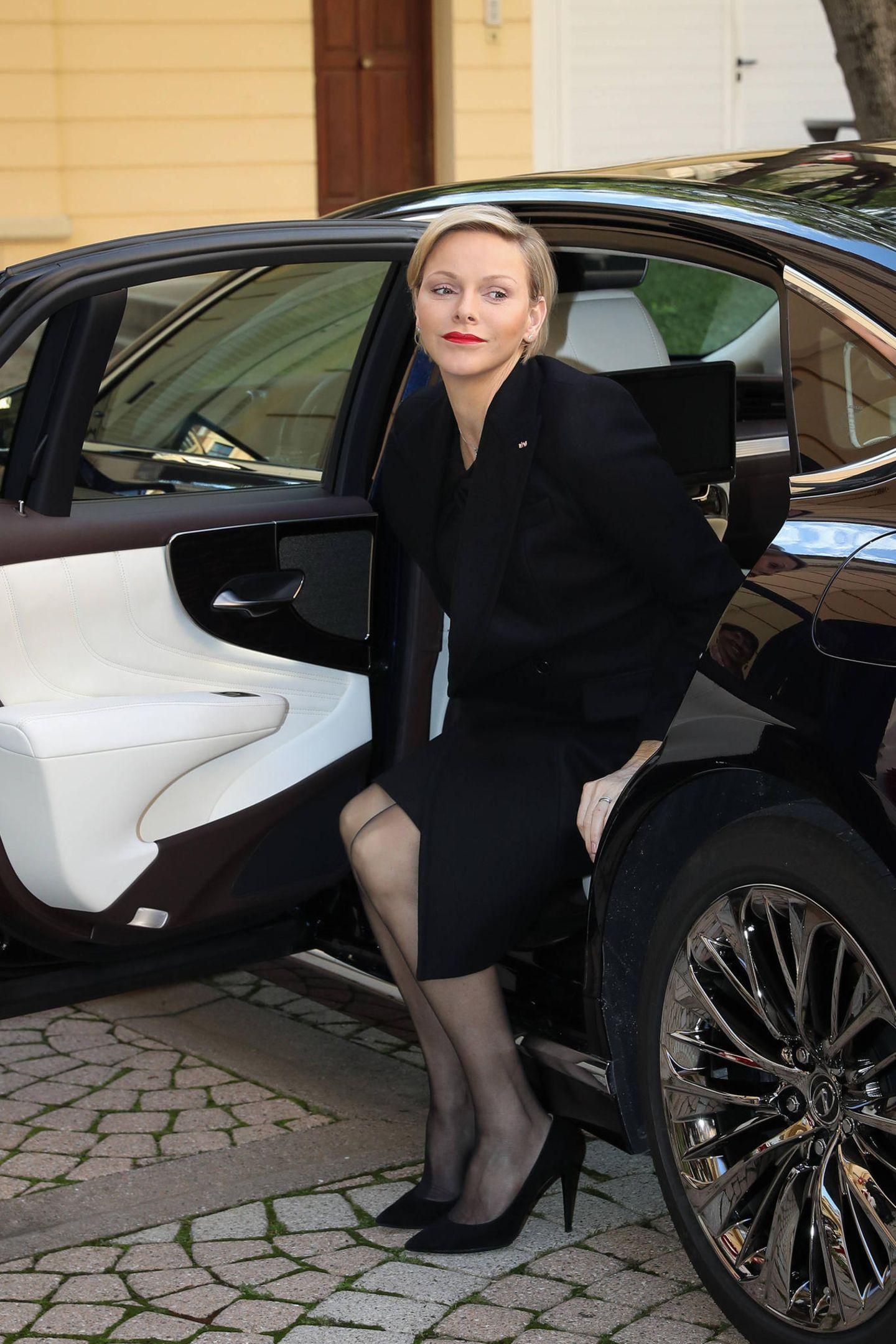 Kurz vor dem Nationalfeiertag Monacos besucht FürstinCharlène das Rote Kreuz, um hier Geschenke zu verteilen. Als sie ankommt, steigt sie äußerst grazil auf ihrem Wagen. Damit ihr Mantel anschließend keine Falten wirft, zieht sie in währenddessen starff.