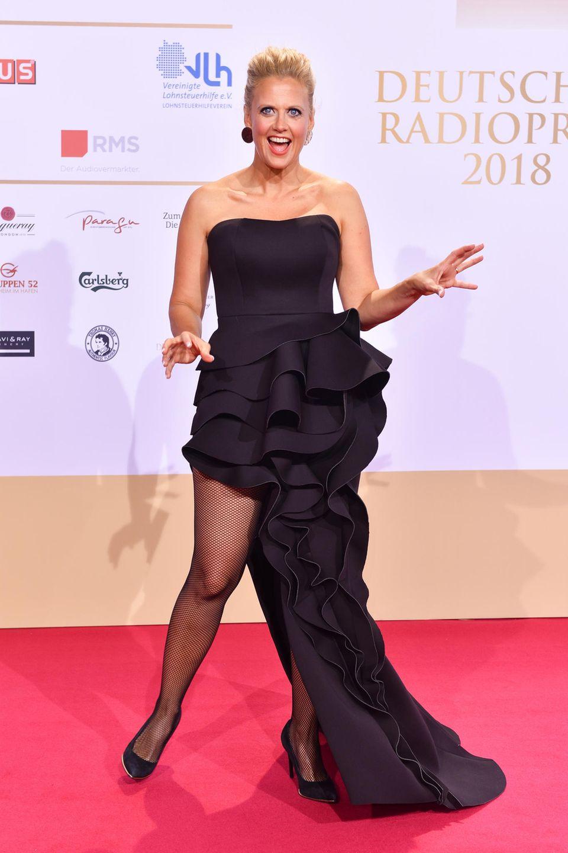 Beim deutschen Radiopreis setzt Moderatorin Barbara Schöneberger auf einen aufregenden Look. Zu einem schwarzen, asymmetrischen Kleid mit ausladenden Rüschen kombiniert sie eine Netzstrumpfhose.