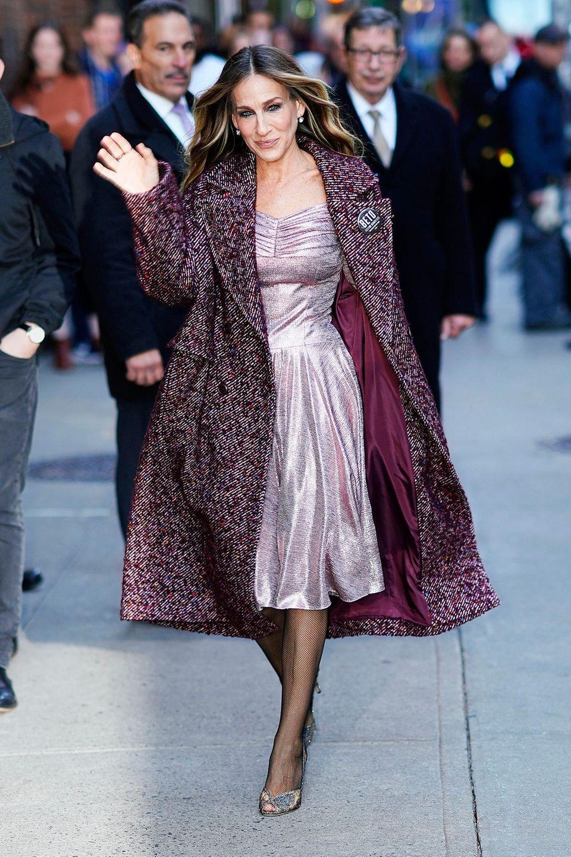 """Sarah Jessica Parker versprüht immer noch """"Sex and the City""""-Charme auf den Straßen New Yorks. Zu einem rosafarbenen Metallic-Kleid kombiniert sie einen herbstlichen Mantel in Bordeauxtönen und glitzernde Peeptoes. Trotz offener Schuhe wählt die Schauspielerin eine Netzstrumpfhose - eigentlich ein Fashion No Go - doch bei Sarah Jessica Parker sieht es super aus."""