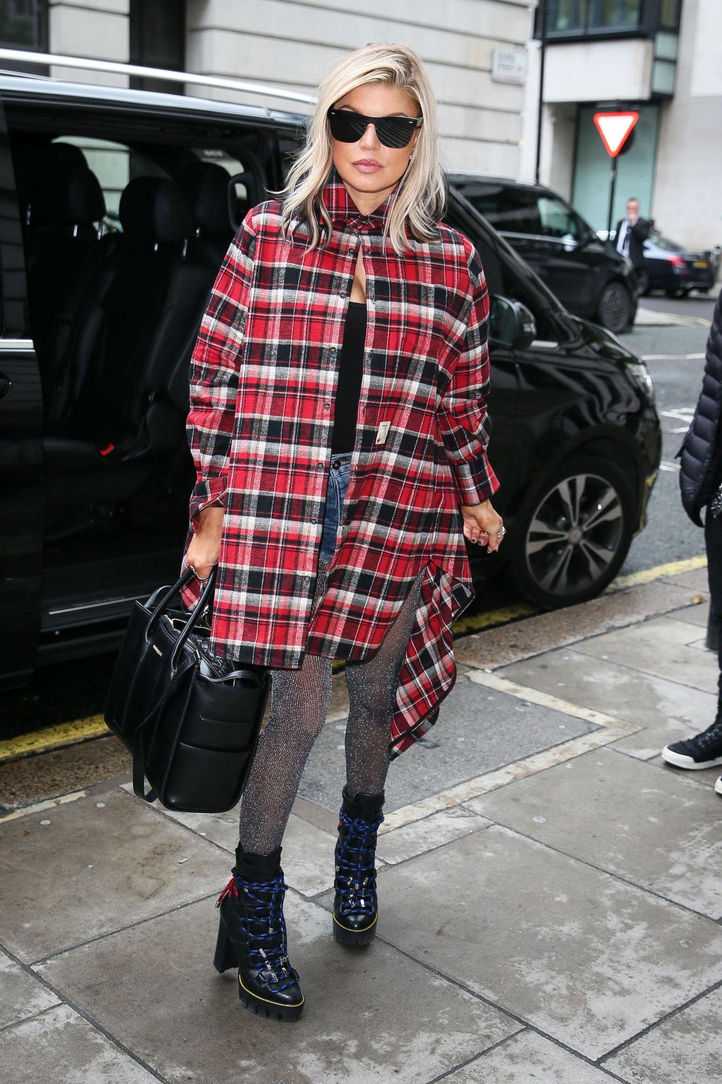 Wilder Style-Mix: Sängerin Fergie ist für ihre coolen Looks bekannt und beweist mit diesem Outfit einmal mehr, dass sie etwas von Mode versteht. Zu einer Jeansshorts kombiniert sie ein schwarzes Oberteil mit Ausschnitt, derbe Boots und ein rot-schwarzes Karohemd. Funkelnder Hingucker ist ihre Glitzer-Strumpfhose.