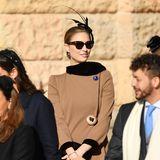 Die große, schwarze Sonnenbrille und das im Nacken geknotete Haar versprühen Glamour pur. Ein besonderer Hingucker istzudem der große Knopf an ihrem Mantel.