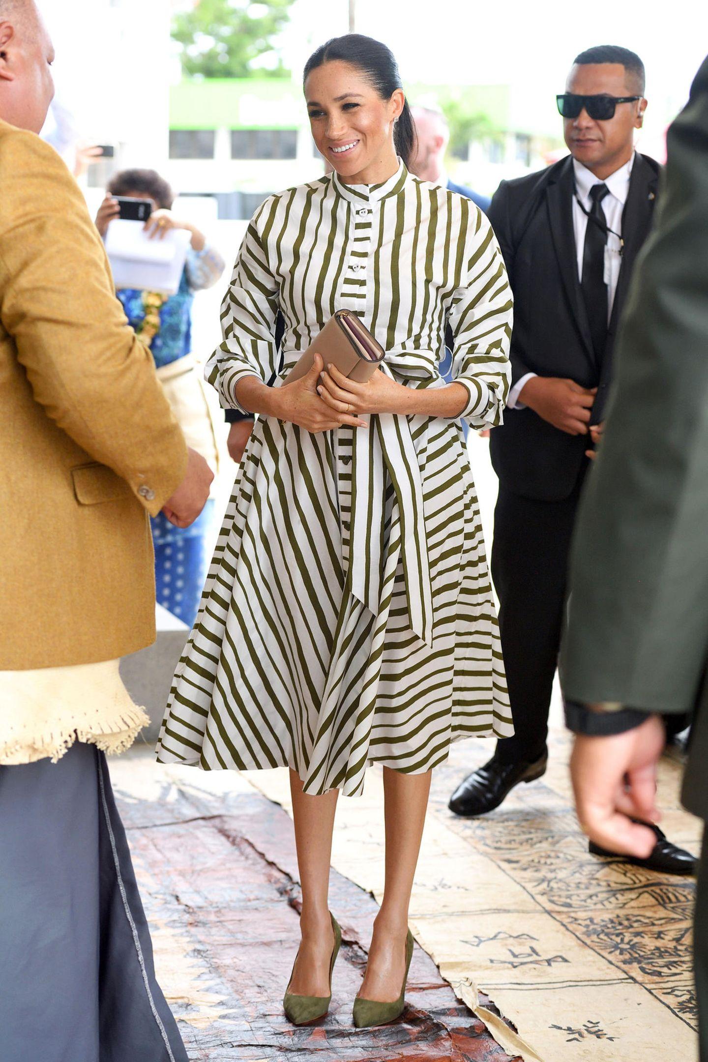 Für das Treffen mit dem Premierminister von Tonga wählt Herzogin Meghan ein grün-weiß-gestreiftes Baumwollkleid des australischen Designers Martin Grant. Das Babybäuchlein wird allerdings hinter ihrer Clutch versteckt