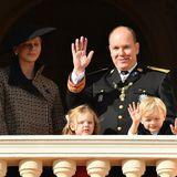 Mutter Charléne hält sich im schattigen Hintergrund, während Fürst Albert II. und die Zwillinge Gabriella und Jacques vom Balkon aus grüßen.