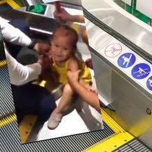 Kleines Mädchen klemmt sich die Finger in der Rolltreppe ein
