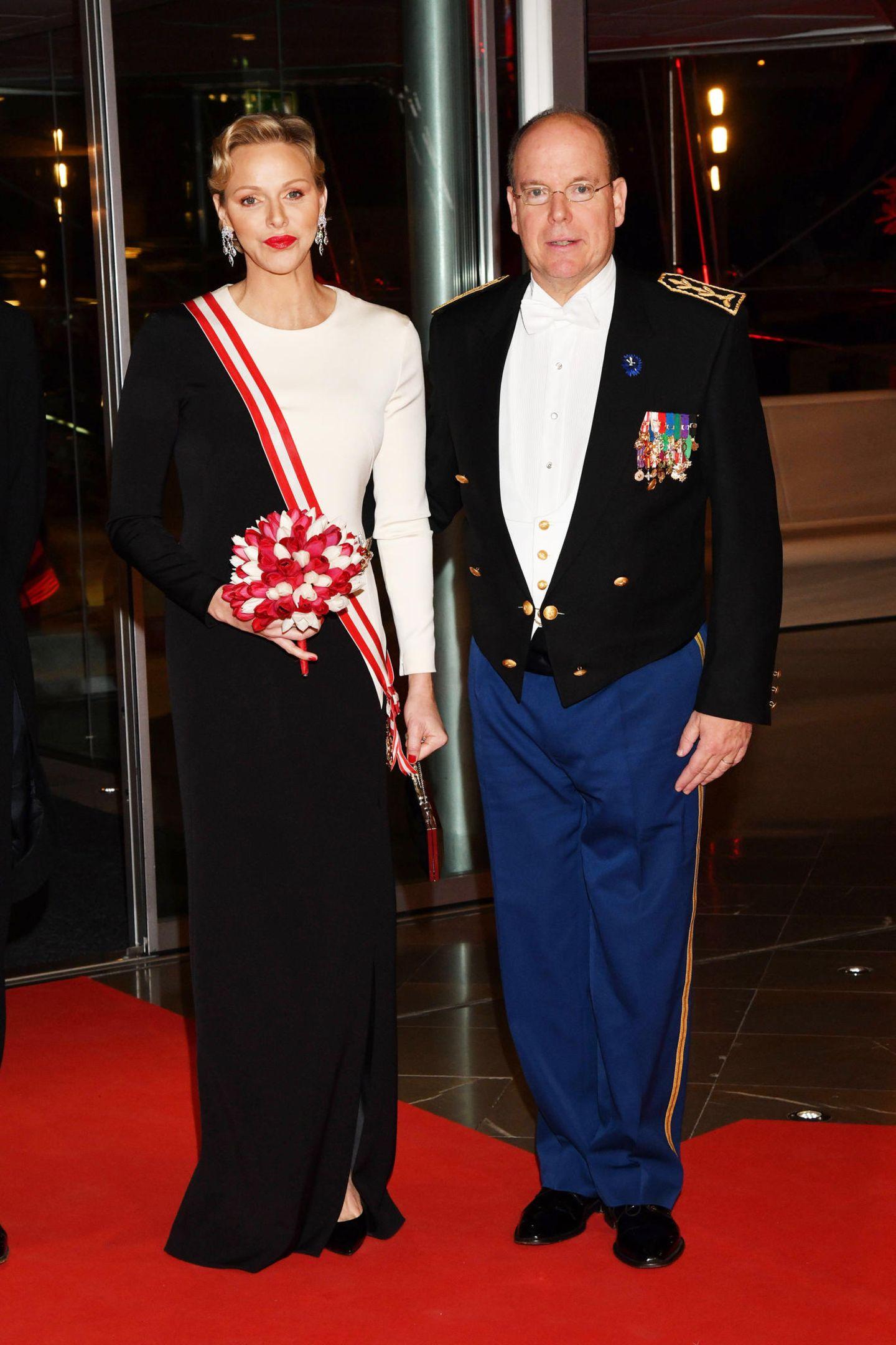 Auch am Abend des Nationalfeiertages in Monaco trägtCharlène zur Gala ein schwarz-weißes Abendkleid. Lediglich ihre rote Schärpe und ihr roten Lippensorgenfür einen kleinen Farbtupfer.