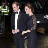 """Herzogin Catherine begleitet Prinz William 2014 zum ersten Mal zur """"Royal Variety Performance"""". Sie wählt ein bodenlanges, mit Spitze überzogenes Kleid in Schwarz. Auch sie hat ein kleines Babybäuchlein vor das sie sich schützend eine schwarz-glitzernde Clutch hält."""
