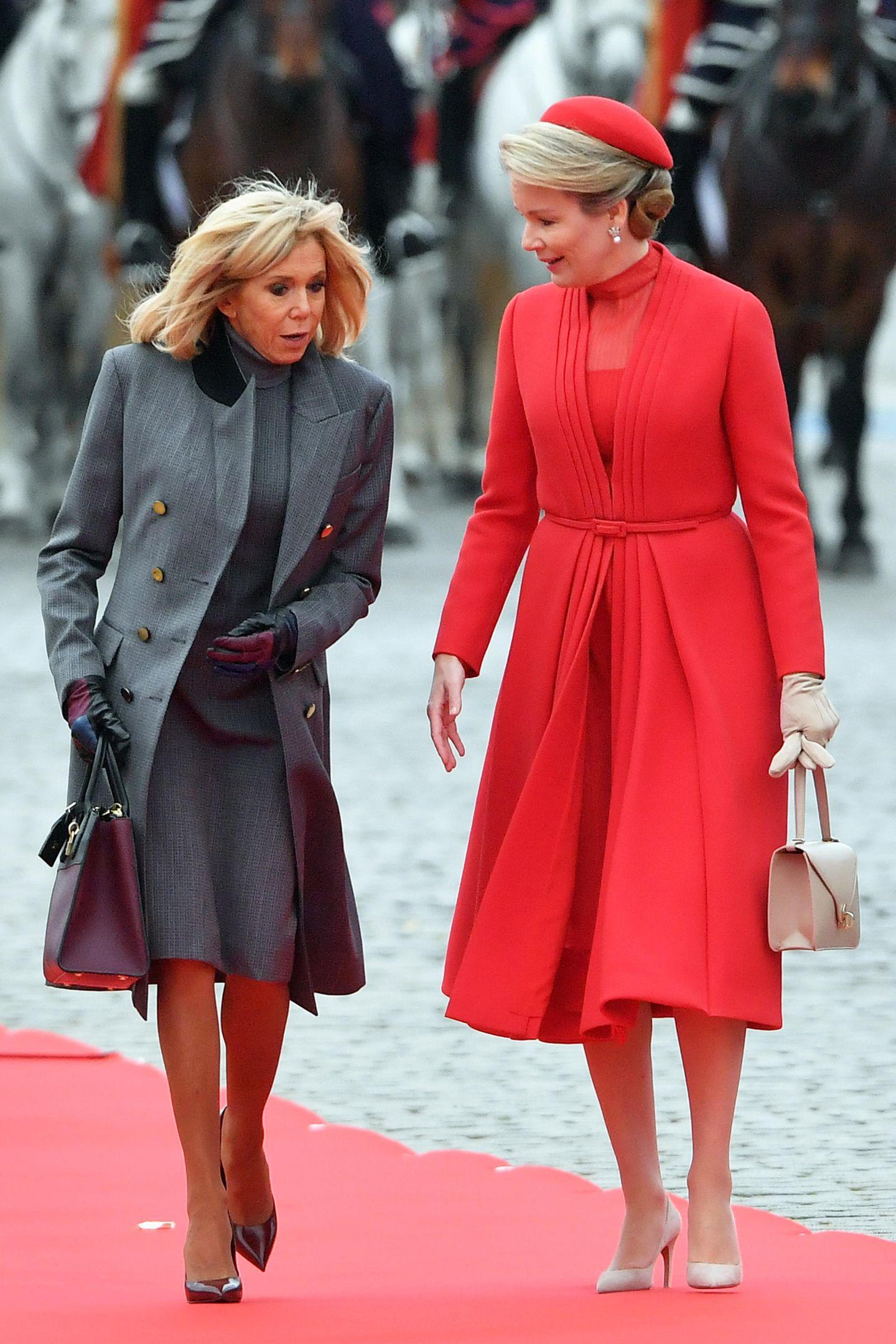 Raffinierte Details: Auf den ersten Blick geht Brigitte Macron in ihrem grauen Look ein wenig unter neben Königin Mathilde. Doch schaut man genauer hin, lässt sich erkennen, dass der doppelreihige Mantel der First Lady mit bunten Knöpfen besticht.
