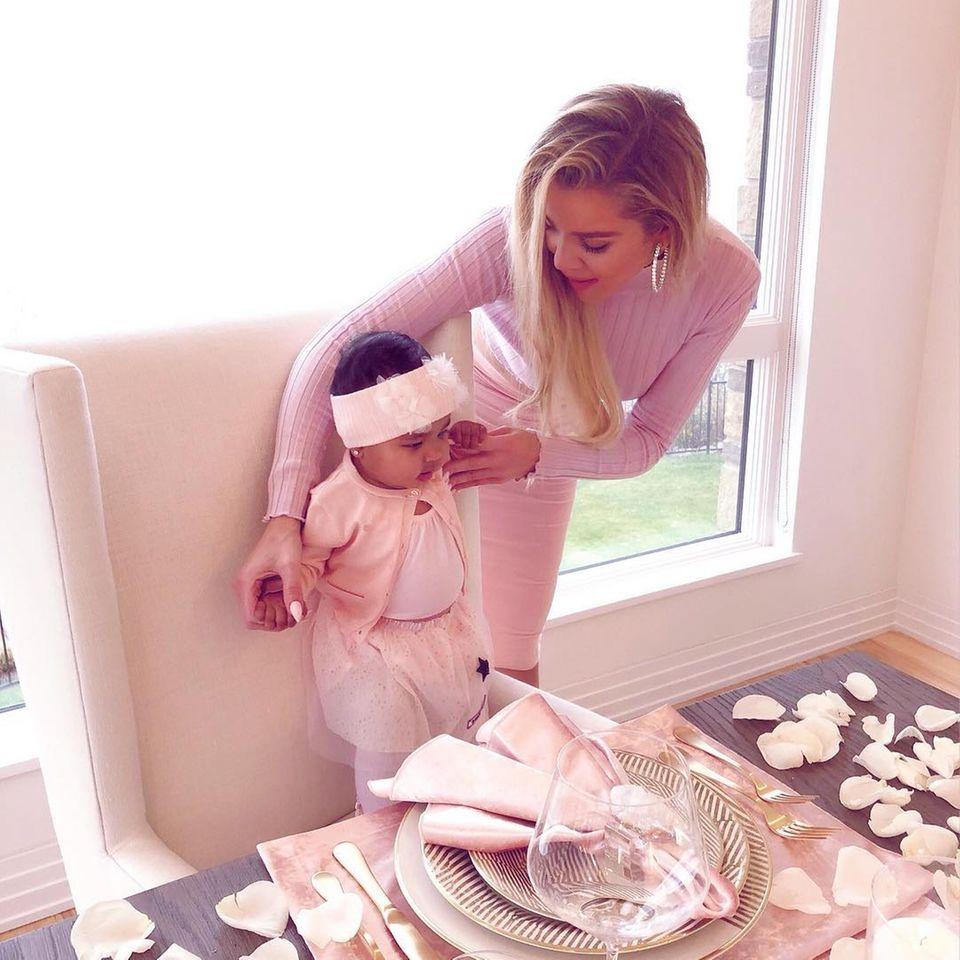 KhloéKardashian zeigt der kleinen True den wunderschön gedeckten Tisch. Natürlich ist die Tochter der jüngeren Schwester von Kim Kardashian passend zur Tischdeko in rosa gekleidet.