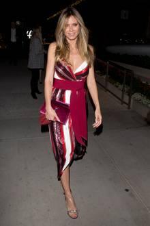Zu einer Party in West Hollywood erscheint Heidi Klum einem einem rot-weiß-gestreiften Kleid von Johanna Ortiz. Die glitzernden Elemente und die dunkelrote Samtclutch machen den Look festlich.