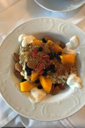 Frühstück à la Monica Meier-Ivancan: Getreidebrei mit gedünsteter Mango, getrockneten Goji und Aronia Beeren, Kokosjoghurt, Wurzelkraftpulver und Mandeln