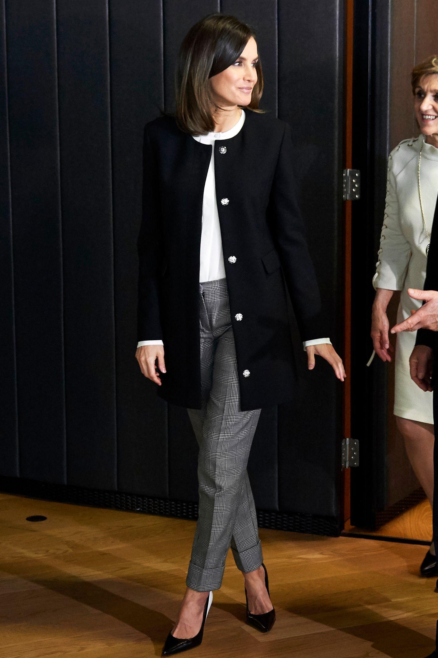 Auf den ersten Blick ist dieser Look von Königin Letizia perfekt. Zu einer grau karierten Hose kombiniert sie eine weiße Bluse und einen schwarzen, dünnen Mantel mit Druckknöpfen. Doch tatsächlich zeigt dieses Outfit mehr als Letizia lieb sein dürfte ...