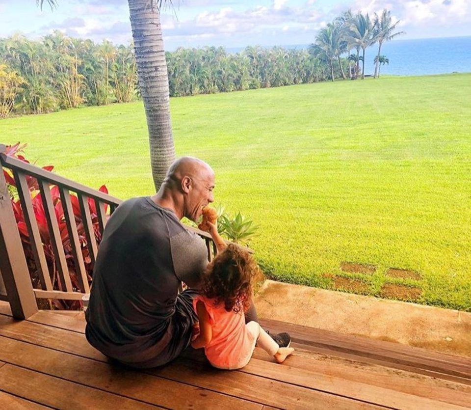 """27. August 2018  """"Sie kann alles werden, was sie will. Sie kann ihrem Papa auch einen Croissant in den Mund stopfen, obwohl er gerade auf strikter Diät ist"""", schreibt Dwayne Johnson scherzend über das Foto mit Tochter Jasmine."""