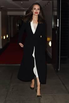 Bei einem Besuch des BFI - einem vom British Film Institute betriebenen Kinos - zeigt sich Schauspielerin Angelina Jolie strahlend schön. Sie trägt ein weißes Midi-Kleid, einen schwarzen Mantel, bronzefarbene Pumps und roten Lippenstift als Akzent. Doch dieses Outfit müssen sie ohne Mantel sehen ...