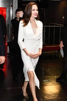 """Erst als Angelina Jolie ihren Mantel fallen lässt, kommt ihr weißes Kleid perfekt zur Geltung. Angelina trägt das """"Belted Wrap Silk Dress"""" des Luxus-Labels Ralph & Russo für knapp 5.543 Euro. Dazu kombiniert die Schauspielerin noch einen breiten Gürtel, sowie ein Spitzen-Top, um nicht so viel Ausschnitt zu zeigen."""